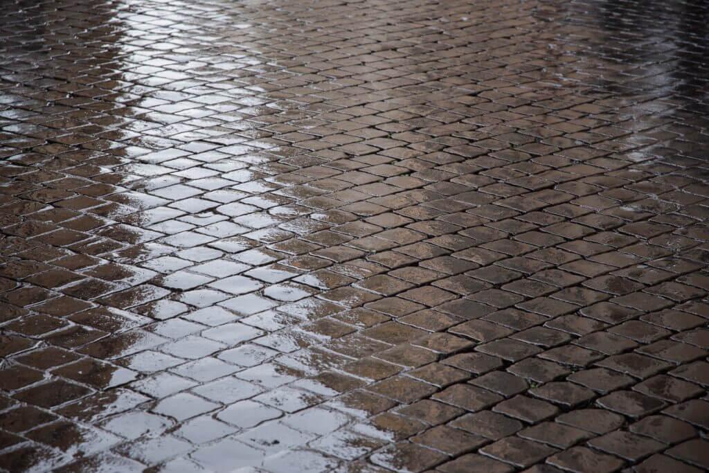Billede af regnvåde brosten i Rom.